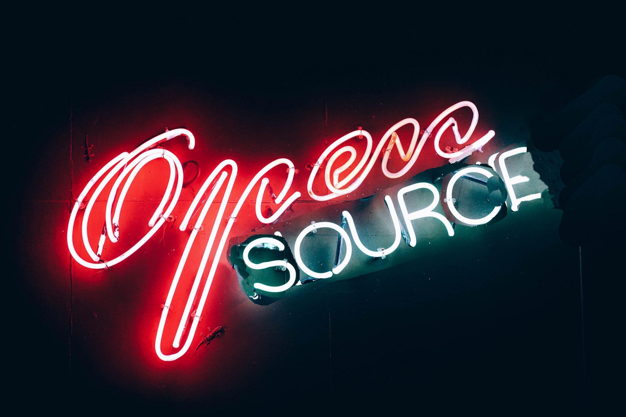 "Photo of Neon sign spelling ""Open Source"""